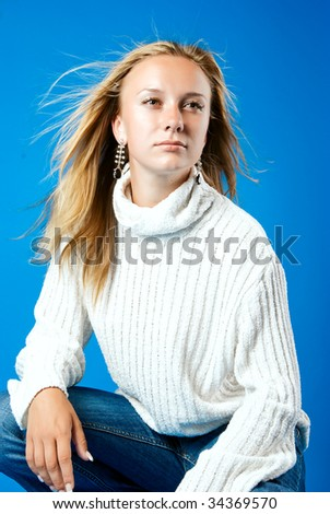 Young blond girl in white sweater sitting - stock photo