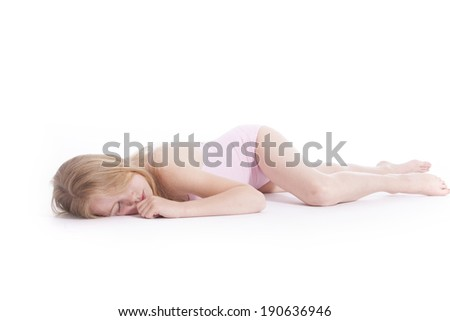 young blond girl sleeping on the floor of studio against white background