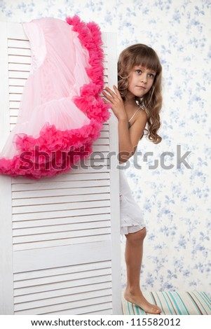 Young blond girl teenager with long wave hair looks out the folding screen when change of clothes - stock photo