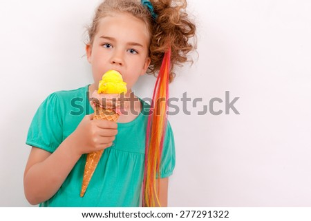 Young blond girl with giants ice-cream cone in hand and co loured tapes in the hair. Studio shot, horizontally with text clearance / Young girl with giants ice-cream cone