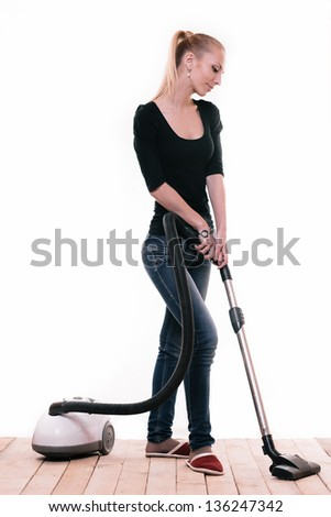 Young blond girl with vacuum cleaner isolated on white