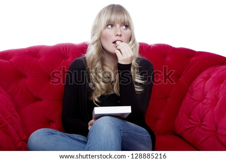 young blond haired girl taste chocolate on red sofa in front of white background - stock photo