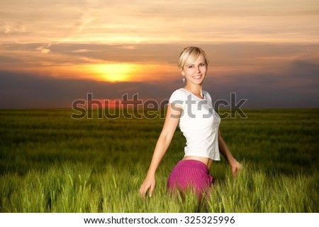 Young blond happy girl in a wheat field at dawn