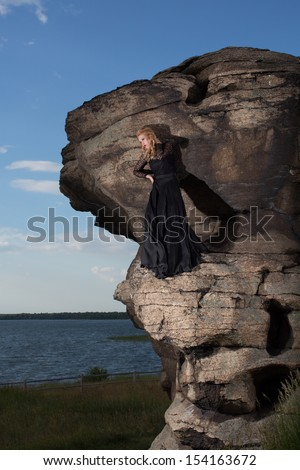 Young blond in a long black dress stands in the middle of the rock against the background of blue sky, lake and grass