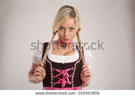 young blond jaunty girl with dirndl and plaits/young blond woman dressed with dirndl for oktoberfest/woman with dirndl and plaits