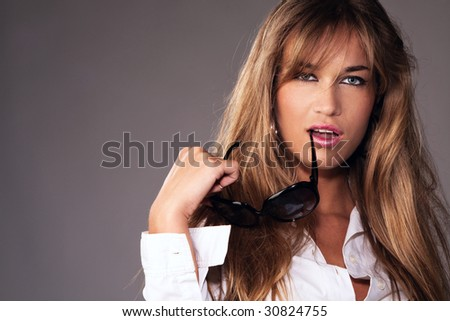 young blond portrait with sunglasses in hand - stock photo