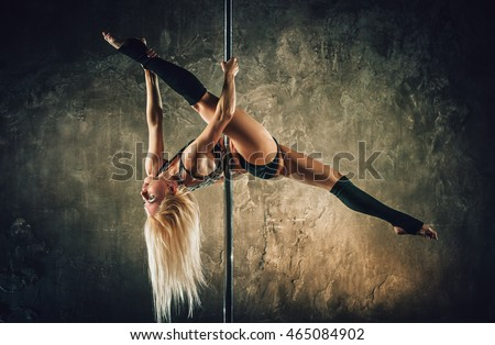 Young blond sexy pole dance woman on old wall background. Film style vintage colors effect.