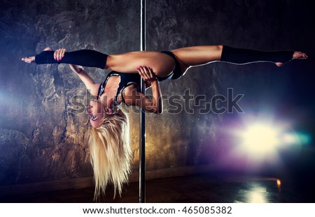 Young blond sexy pole dance woman on old wall background with flare effect