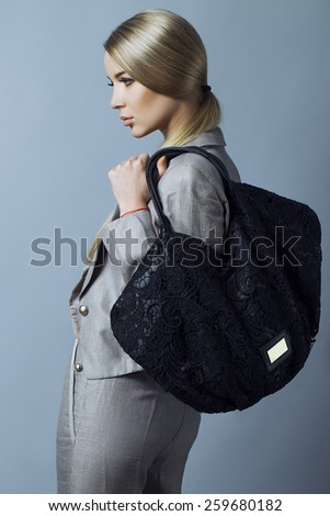 Young blond sexy woman in a business suit and with black fishnet bag on a grey background. Long legs. Studio shot - stock photo