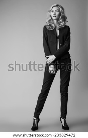 Young blond sexy woman in a business suit on a grey background. Long legs. Studio shot - stock photo