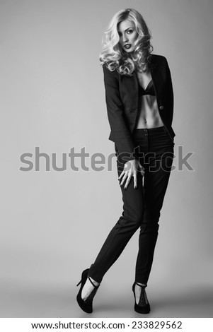 Young blond sexy woman in a business suit on a grey background. Long legs. Studio shot