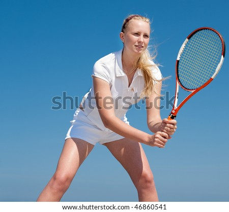 Young blond  tennis-player in white sportwear outdoors - stock photo