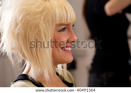 young blond woman at hairdresser, indoor shot - stock photo