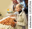 Young blond woman choosing fresh eggs on market - stock photo