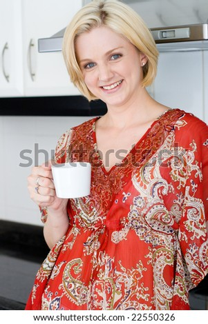 Young blond woman drinking coffee in the kitchen - stock photo