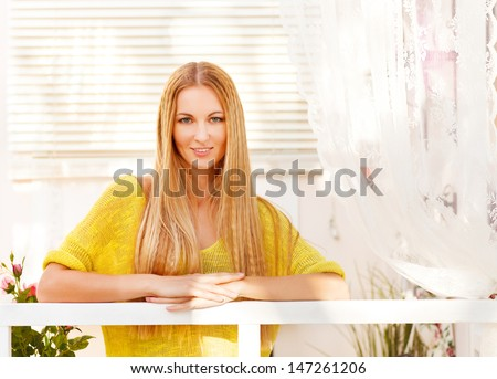 Young blond woman enjoying her comfortable terrace - stock photo