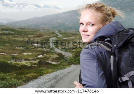 young blond woman hiking with scenery in the background - stock photo