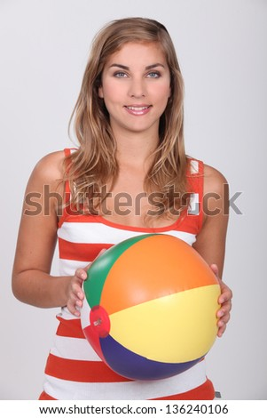 Young blond woman holding beach ball - stock photo