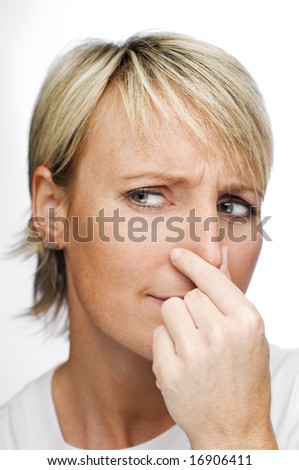 young blond woman holding her nose because of a bad smell