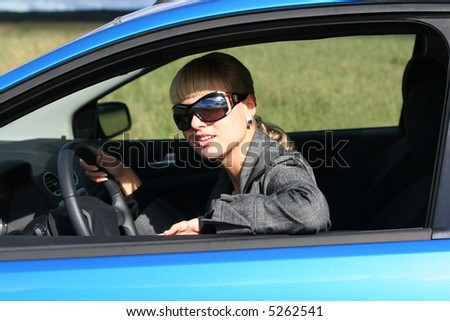 young blond woman in a blue car in sun-glasses - stock photo