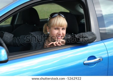 young blond woman in a blue car/ She is smiling happy - stock photo