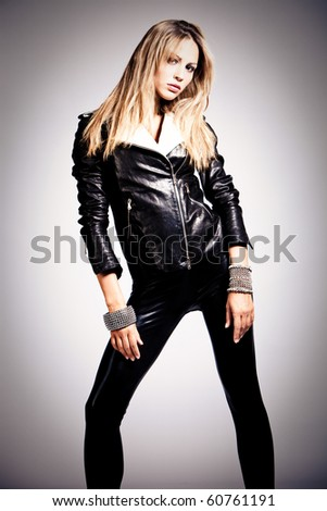 young blond woman in black leather, studio shot - stock photo