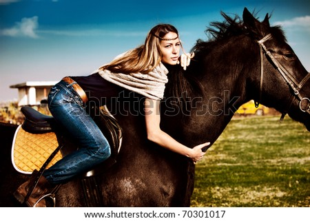 young blond woman in blue jeans on a horseback, late summer day