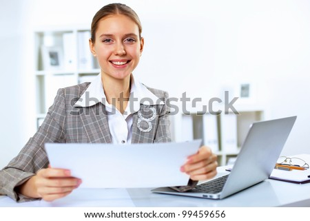 Young blond woman in business wear in office environment - stock photo