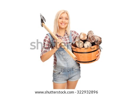 Young blond woman in checkered shirt holding a bucket full of logs and carrying an axe over her shoulder isolated on white background - stock photo