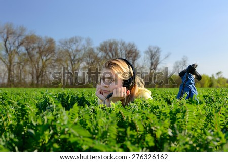 Young blond woman in headphones lying on the grass in the field - stock photo