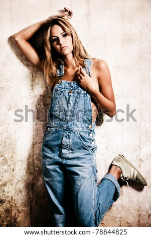 young blond woman in jeans against wall - stock photo