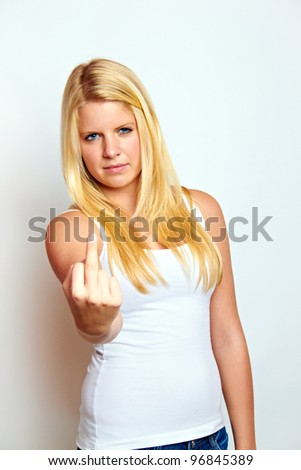 young blond woman is showing the middlefinger - stock photo
