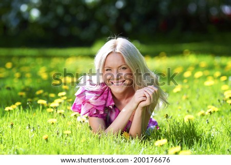 Young blond woman laying in a meadow with dandelions - stock photo