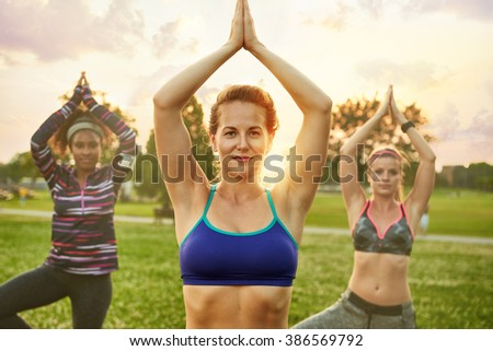 Young blond woman leading a yoga class at sunset in nature park  - stock photo