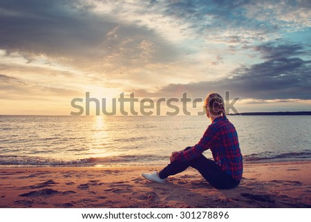 young blond woman looking at setting sun