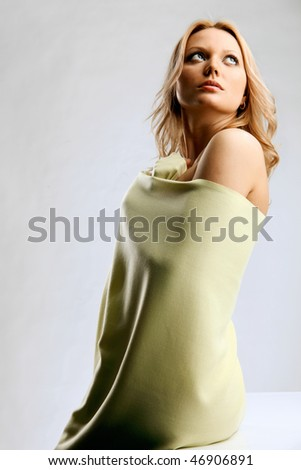 Young blond woman looking up wrapped in light-yellow cloth - stock photo