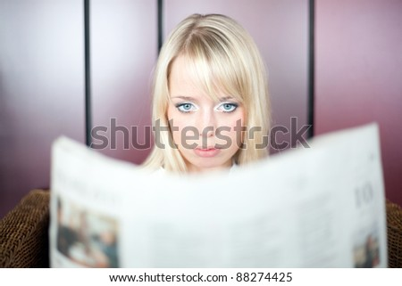 young blond woman looks in a newspaper and is shocked/woman with a newspaper - stock photo
