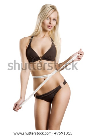 young blond woman measuring her body with a tape and looking in camera . healthy lifestyles concept - stock photo