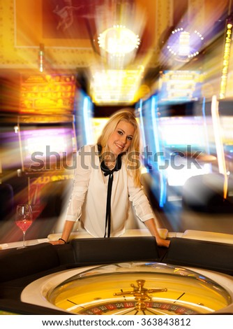 Young blond woman playing roulette in casino and winning - stock photo