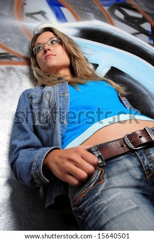 young blond woman pose in front of graffiti - stock photo