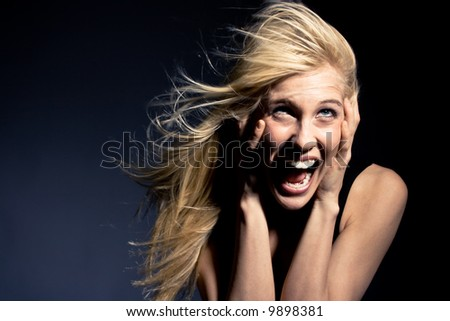 young blond woman screaming in fear, studio - stock photo