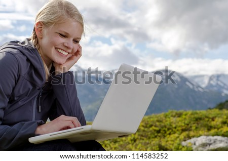 young blond woman sits with a laptop before a mountain landscape - stock photo