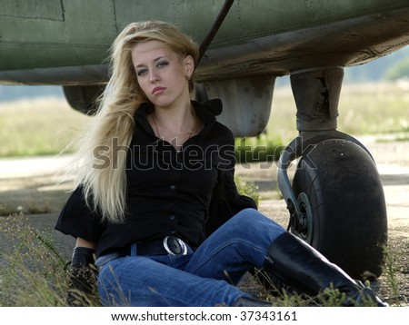 Young blond woman sitting on ground near vintage airplane - stock photo