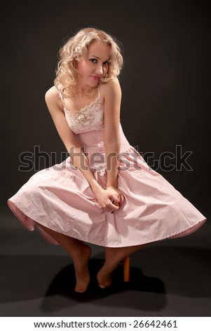 Young blond woman sitting on stool