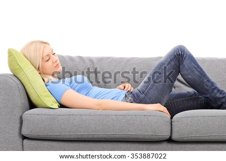 Young blond woman sleeping on a gray couch isolated on white background - stock photo