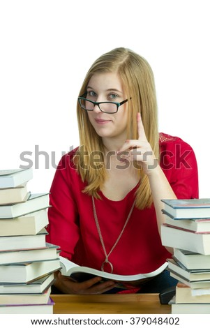 Young blond woman studying with stacks of books - stock photo