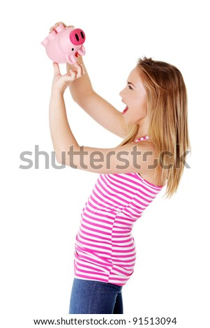 Young blond woman trying to get money from her piggy bank - stock photo