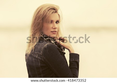 Young blond woman walking in a fog. Female fashion model in denim jacket outdoor - stock photo
