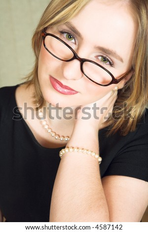 Young blond woman wearing glasses with tired expression on her face, rubbing her neck - stock photo
