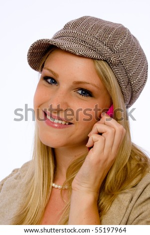 Young blond woman wearing mod cap talks on cell phone and smiles at camera. - stock photo